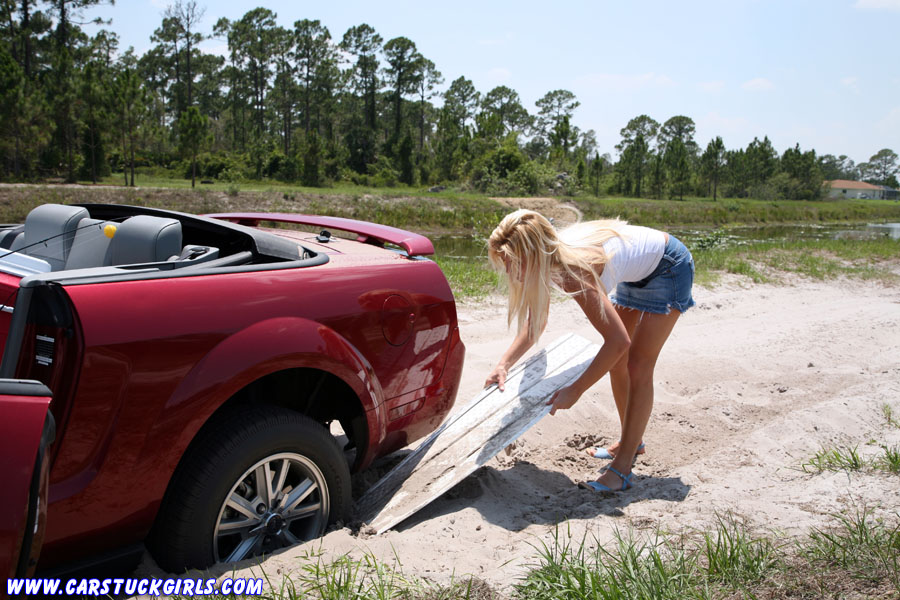 Sexy hot blonde mustang convertible stuck in sand